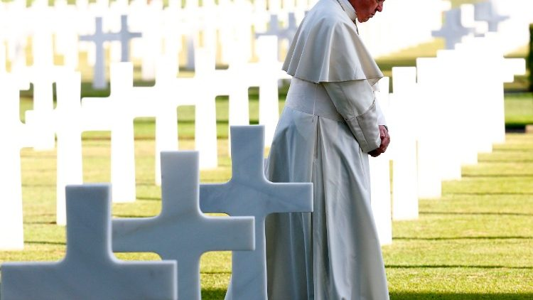 Pope Francis lays white roses on tombs at the US war cemetery in Nettuno south of Rome before celebrating Mass.