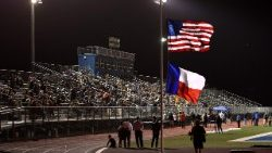 A file photo of the American and Texan flags flying at half-mast in a football stadium