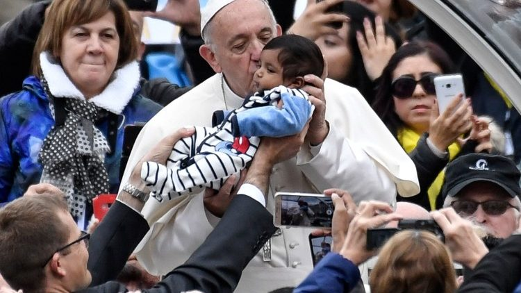 The pope kisses a baby