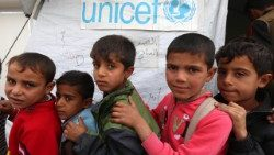 Displaced Iraqi children queue up outside a school funded by UNICEF