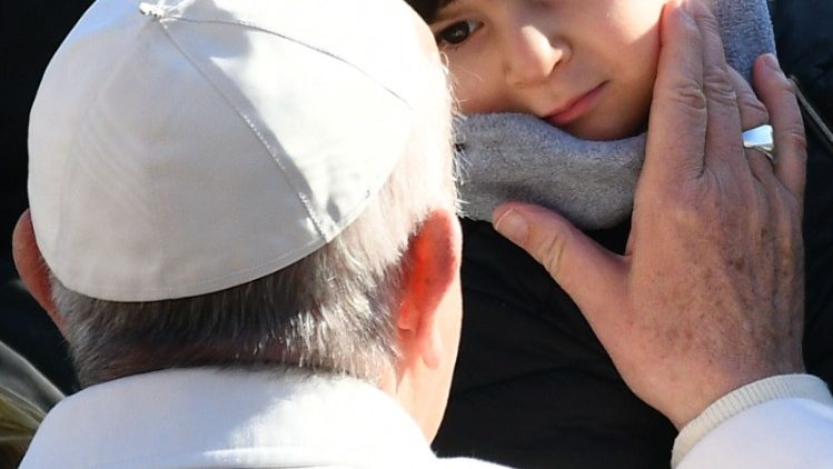 Pope caresses the face of a child at his general audience