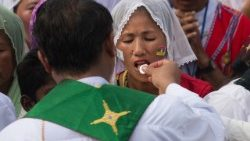 A woman receives communion at Mass in Yangon, Myanmar