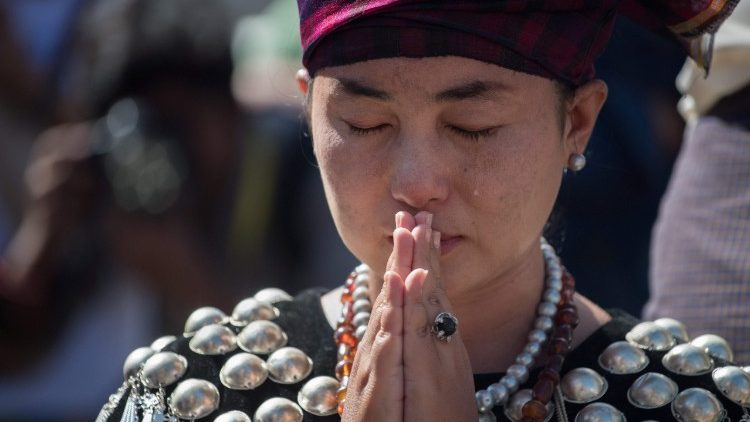 A woman from Kachin State in Myanmar prays outside St. Mary's Cathedral during a Mass celebrated by Pope Francis in Yangon