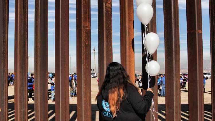 A woman stands at the border between the United States and Mexico. From January 7-13, the U.S. Bishops observe National Migration Week, celebrating the immigrant nature of America.