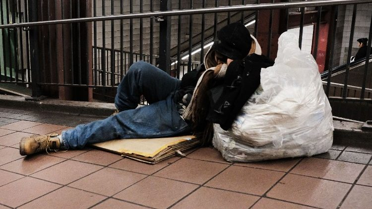 A homeless man sleeps on the ground in New York City