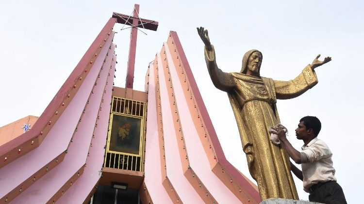 An Indian worker cleans the statue of Jesus ahead Christmas celebrations