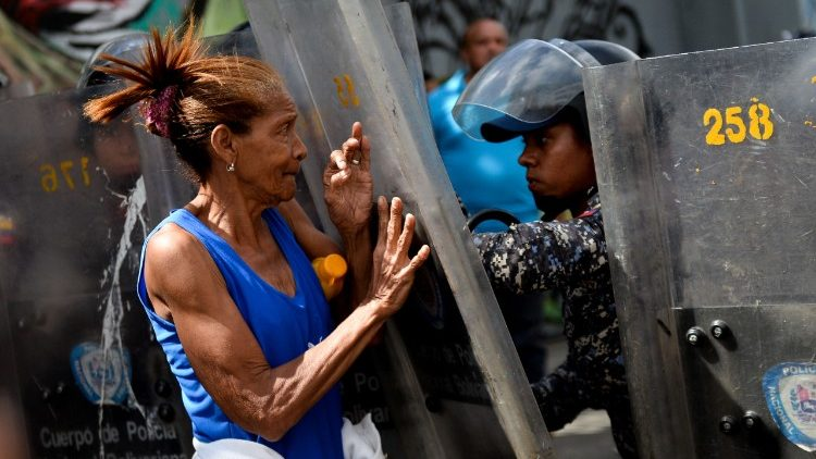 A protester confronts riot police during a protest against food shortage in Caracas