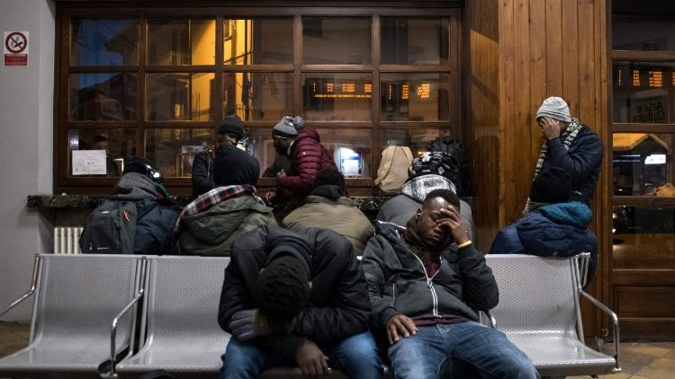 Migrants waiting at a train station in Italy.