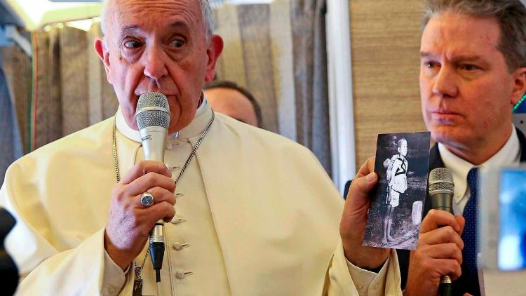 Pope Francis holds a photo of a Japanese boy waiting to cremate the body of his brother in Nagaaki in 1945