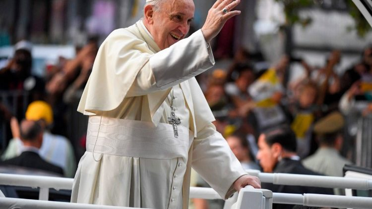 Pope Francis waves at the crowds from the Popemobile in Santiago