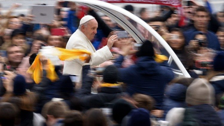 Pope Francis greets the faithful in St. Peter's Square as he arrives for the General Audience
