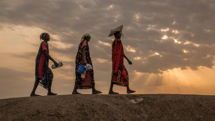 Internally displaced women walk to a food distribution centre in Bentiu, South Sudan