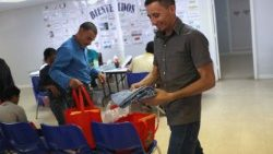 Catholic Charities gives a Honduran immigrant a pair of pants for his son