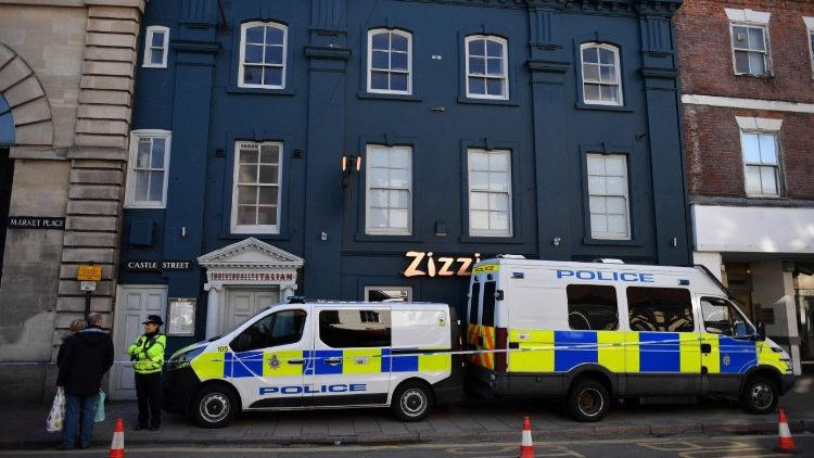 Police stand guard outside a restaurant in England where a former Russian spy was believed to have been poisoned