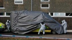 Personnel in protective coveralls work at the site of the incident in Salisbury, England