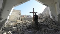 Member of the Syrian Arab-Kurdish forces places a cross in the rubble, Raqa, Syria