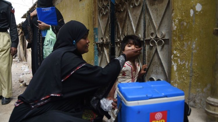 A Pakistani health worker administering polio vaccine to a child.