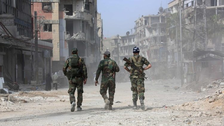 Syrian government forces walk along a ruined road in Eastern Ghouta