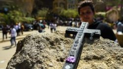 A man looks at an Egyptian Coptic cross placed on a rock