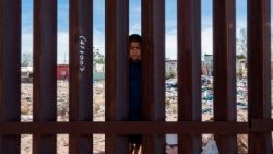 Mexican boy peering over the Border Fence in Anapra, near El Paso, Texas