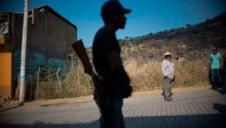 A Mexican community police member stands guard in an area where people have taken the fight against organized crime into their hands