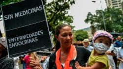 A Venezuelan woman with her sick daughter takes part in a protest by health workers and patients for the lack of medicines, medical supplies and poor conditions in hospitals