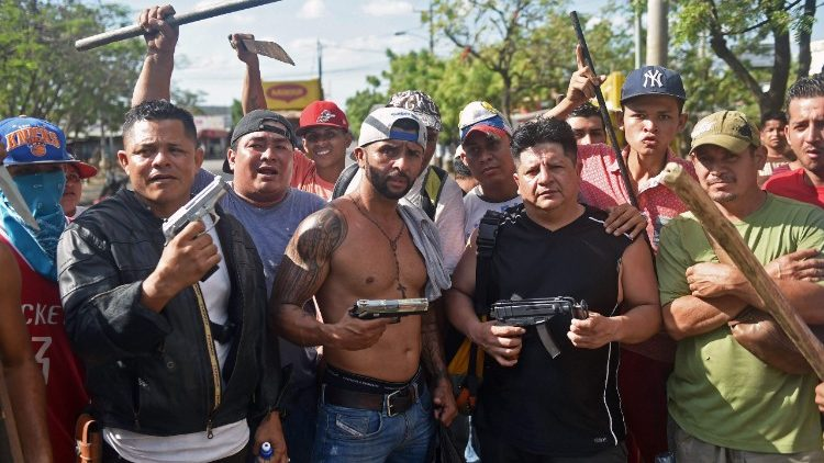 Armed shopkeepers in Managua guard their businesses amid lootings during protests against the government's pension reforms
