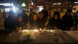 People lay candles and leave messages at a memorial for victims of a vehicular attack in Toronto, Canada