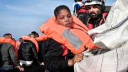 A pregnant woman is transferred to the rescue boat during a rescue operation off the Libyan coast