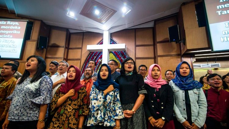 Indonesians from various religious backgrounds pray for victims of a bomb attack on a church.