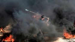 A Palestinian man uses a slingshot to throw a stone towards Israeli forces