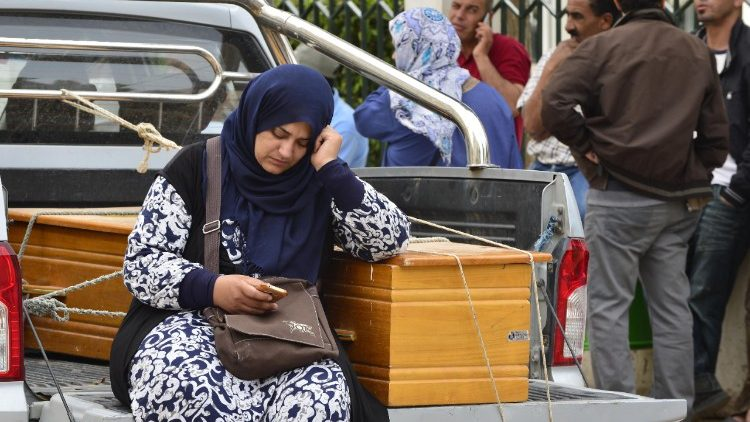 A woman sits next to the coffin of a drowned loved one off the coast of Tunisia