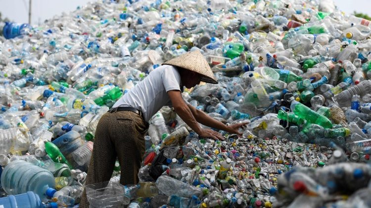 A man sorting through used plastic bottles at a junkyard in Hanoi