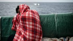 A migrant rests on the deck of a rescue ship after being pulled from the water