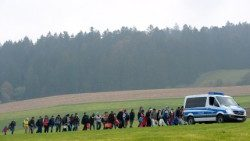 Migrants walk behind a police car on their way from the Austrian-German border to a first registration point of the German federal police in Bavaria