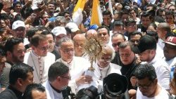 Cardinal Leopoldo Brenes holds the Blessed Sacrament in a crowd of worshipers