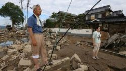 residents look at debris scattered across a flood hit area in Kurashiki
