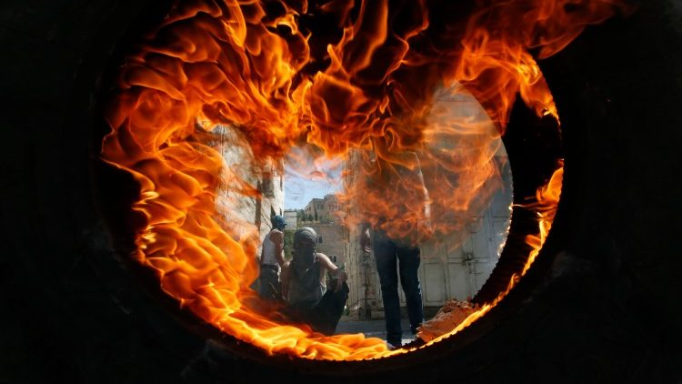 Palestinian protesters seeen through a burning tyre during clashes with Israeli soldiers in Hebron