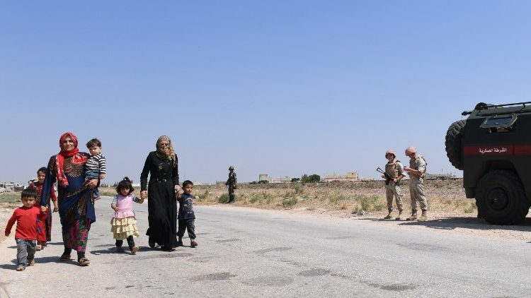 Syrian families walk as Russian and Syrian forces stand guard