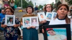 Relatives holding pictures of missing loved ones in Monterrey, Mexico, on the International Day of the Victims of Enforced Disappearance