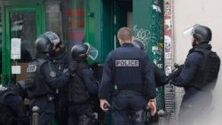 French Police officers enter a building during a police operation in Paris