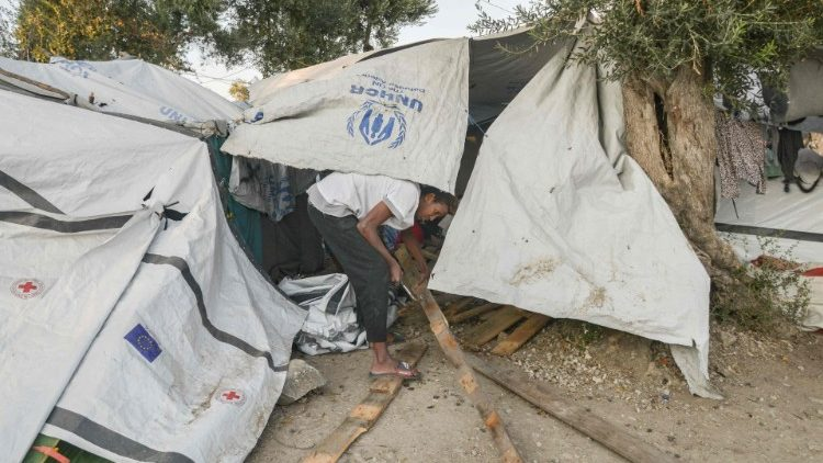 A  man fixes his tent in a camp outside of the refugee camp of Moria on the island of Lesbos