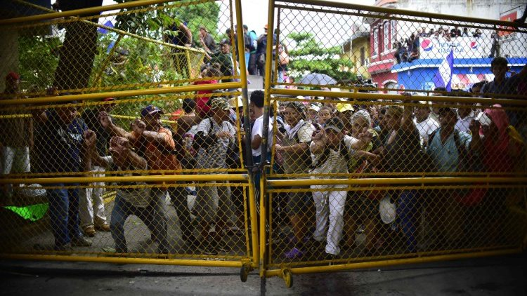Migrants heading to the US try to push through a gate at the Guatemala/Mexico border