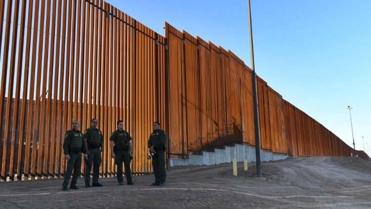 US Border Patrol Officers stand beside a completed section of the wall along the border between the United States and Mexico.