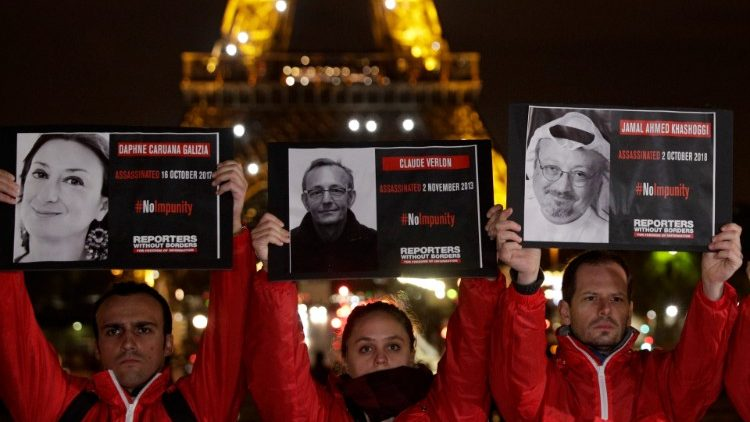 Demonstrators holding portraits of killed journalists in front of the Eiffel Tower in Paris, France, on the eve of the International Day to End Impunity for Crimes against Journalists.