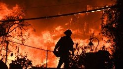 A firefighter silhouetted by a burning home in Malibu, California