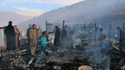 Syrian refugees amidst the charred ruins of their camp in Yammouneh in Lebanon.
