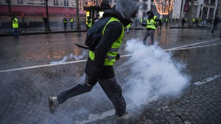 French protesters run as police lob tear gas near the Champs Elysees Avenue