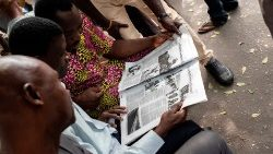 Nigerians read about the postponement of elections in a daily paper