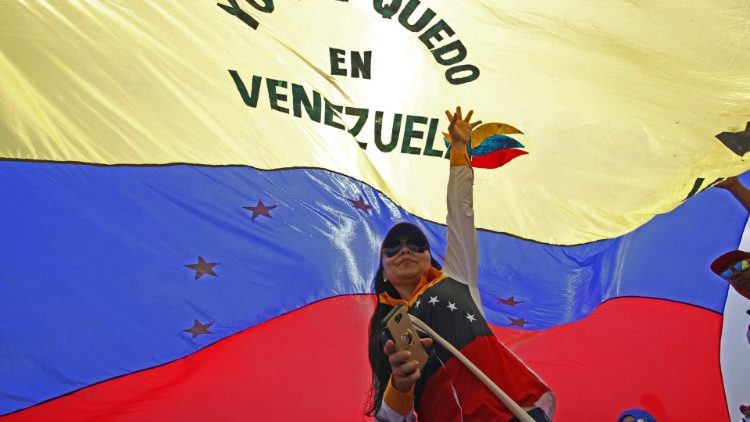"A woman hold Venezuelan flag as she participates in ""Venezuela Aid Live"" concert"